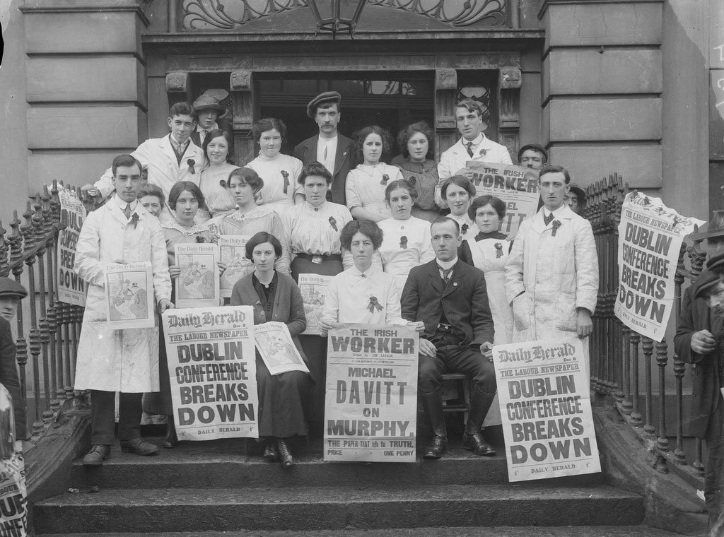 Workers on the steps of Liberty Hall carry news posters announcing the failure of the Dublin Peace Conference, December 1913. Front and centre, holding The Irish Worker poster, is Delia Larkin, sister of Jim Larkin and first General Secretary of the Irish Women Workers' Union, founded in 1911.