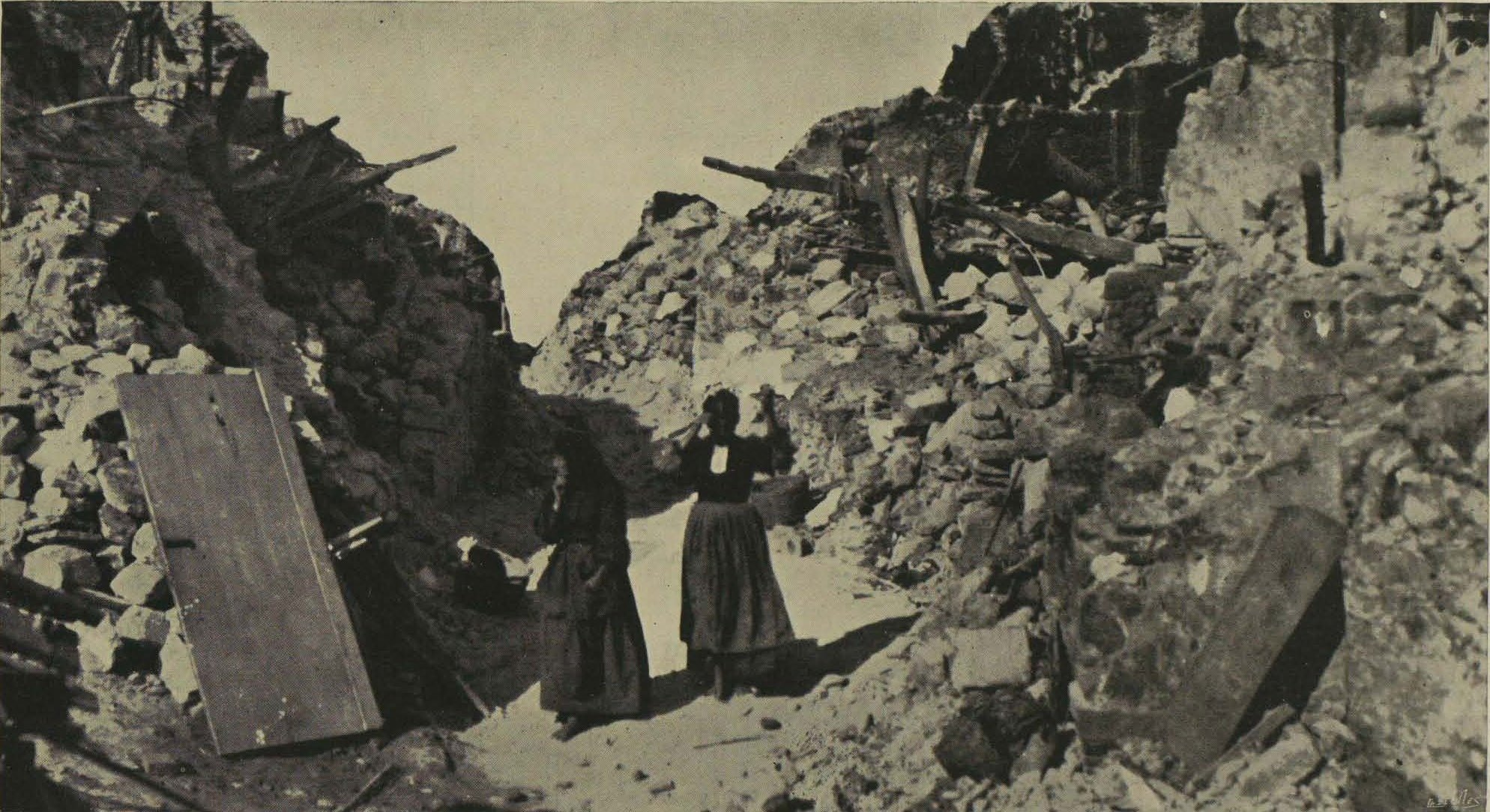 Homeless women standing in the ruins of where their houses once stood.