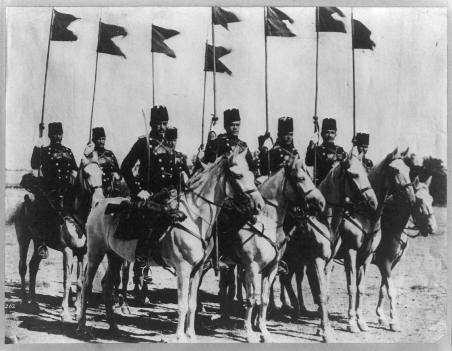 Eight members of the Turkish cavalry on horseback with flags  ca. 1913. Reports from Bulgaria claim that Turkish troops have committed a series of atrocities in the country